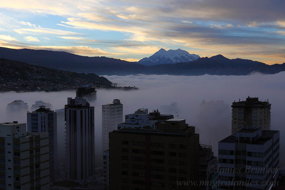 Early morning mist in valley in city centre at sunrise, Mt Illimani in background , La Paz , Bolivia